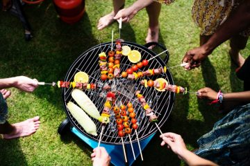 People barbecuing skwered meats on the best portable grill