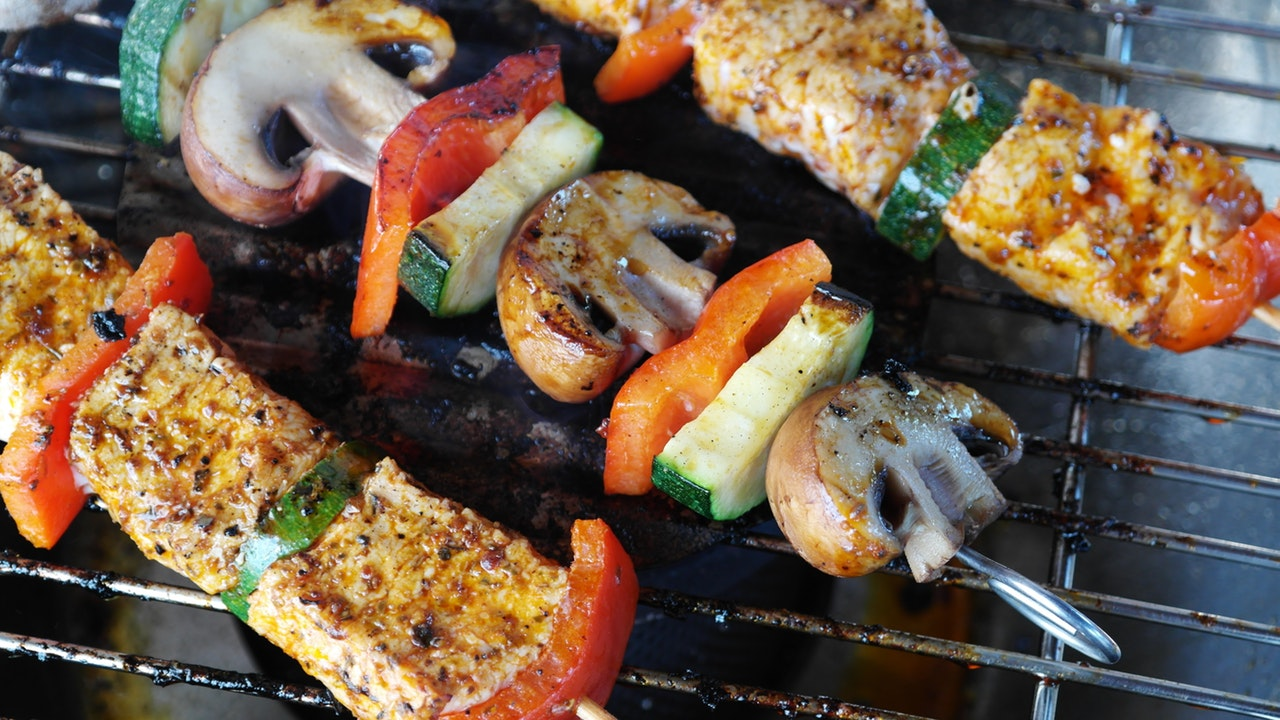 Barbeque sticks with meats and vegetable on top of a grill