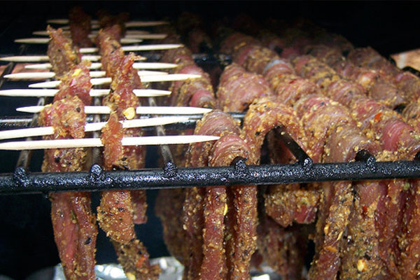 raw jerky hanging in smoker
